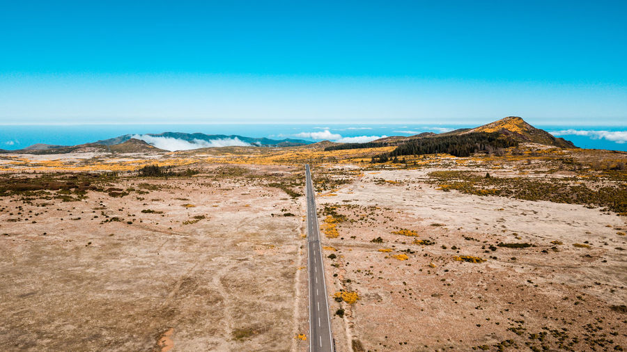 """The longest straight road in """"Paul da Serra"""", Madeira island, Portugal, on a sunny day Above Aerial View Aerial Photography Aerial Shot High Angle View Drone  DJI Mavic Pro DJI X Eyeem Asphalt Countryside Day Daylight Destination Tranquility Travel Destinations Travel Beauty In Nature Outdoors Paul Da Serra Perspective Highway Road Street Environment Nature Non-urban Scene No People Scenics - Nature Semi-arid Summer Vacations Holiday Adventure Mountain Way"""
