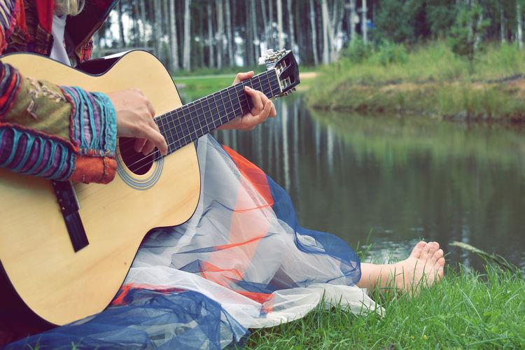 Man playing guitar on lake