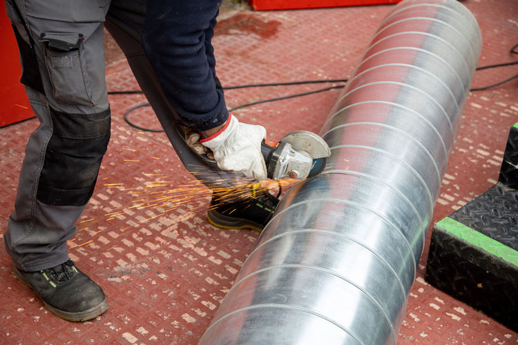 Low section of manual worker cutting metal pipe with grinder