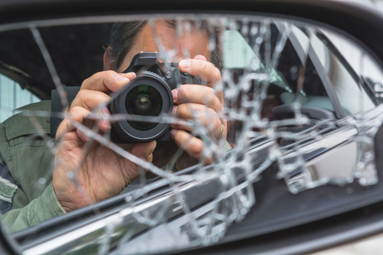 Reflection of man photographing on shattered side-view mirror