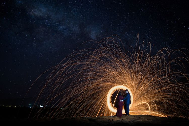 Full length side view of couple standing face to face by spinning wire wool against star field at night