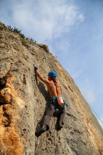 Shirtless climber man climbing mountain wall on amazing sunny day Man Climbing Climber Mountain Rock Cliff Sunny Shirtless Sport Extreme Sports Activity Height Rope Challenge Strong Adventure RISK Exercising Grip Young Adult Fearless Athlete Training Difficult Carabiner