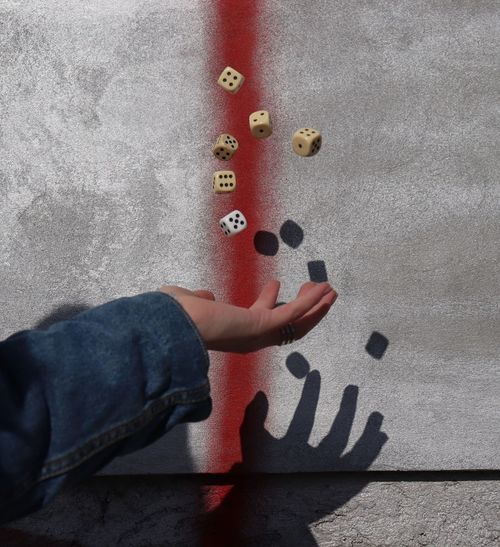 Close-up of person throwing dices against wall