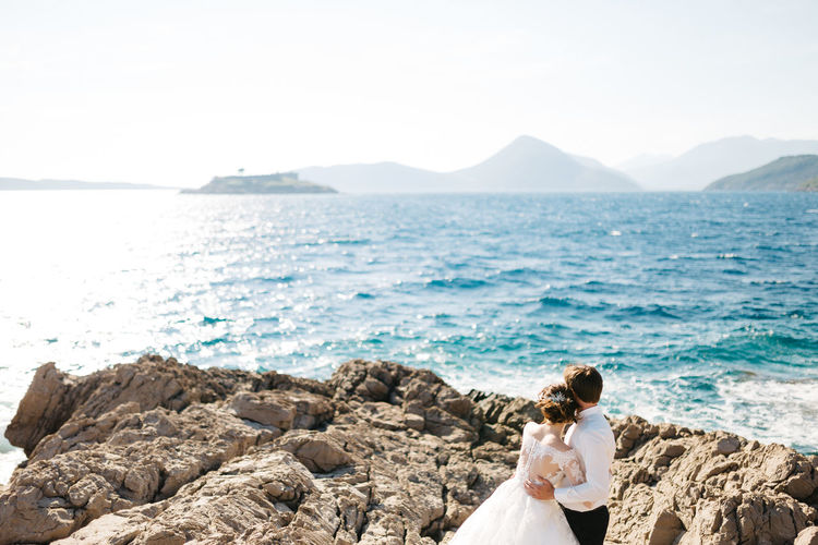 Couple standing by sea against sky