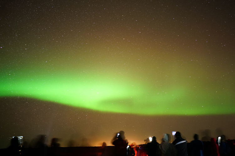 Blurred motion of people with aurora borealis in sky at night