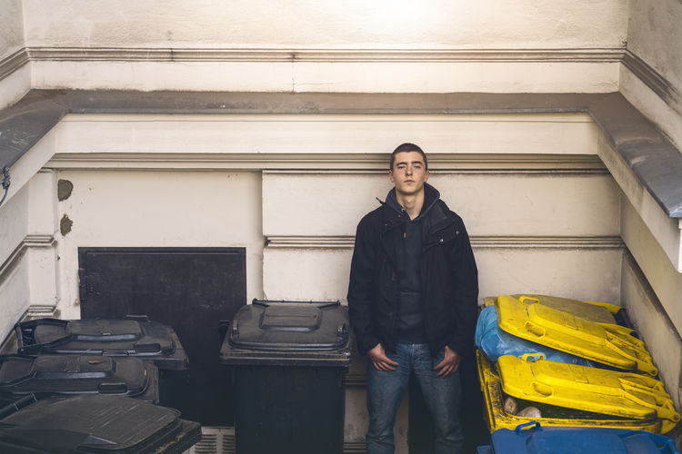 Portrait of young man standing by garbage bins against wall