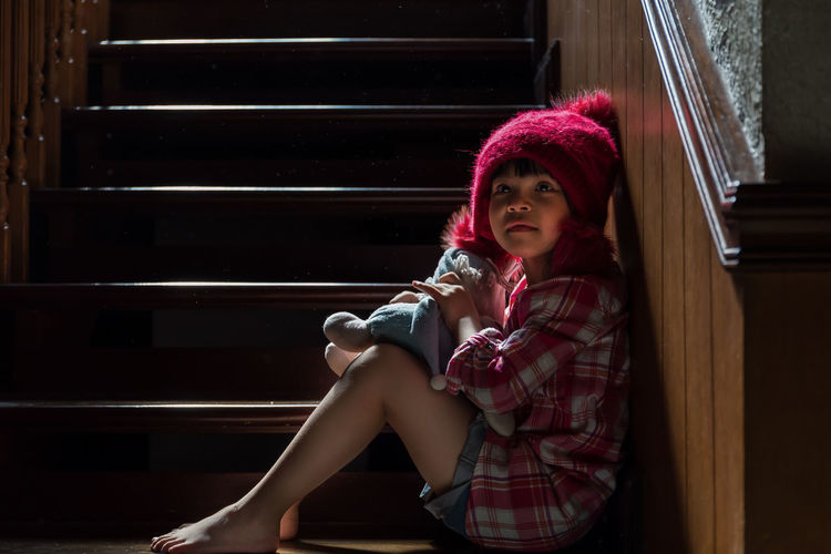 Cute Girl With Toy Sitting On Steps At Home