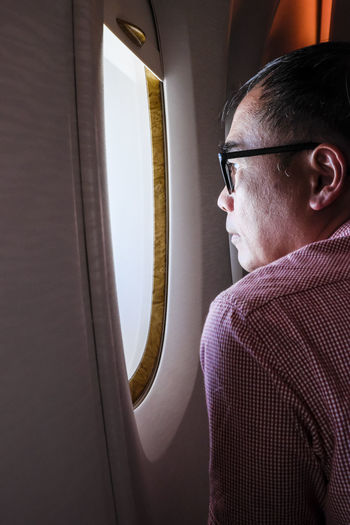 Side view of an adult man looking out of an airplane window Adult Asian  Looking Out Of The Window Man Passenger Travel Air Travel  Airplane Airplane Cabin Economy Class Eyeglasses  Flying Inflight Lifestyles One Person People Side View