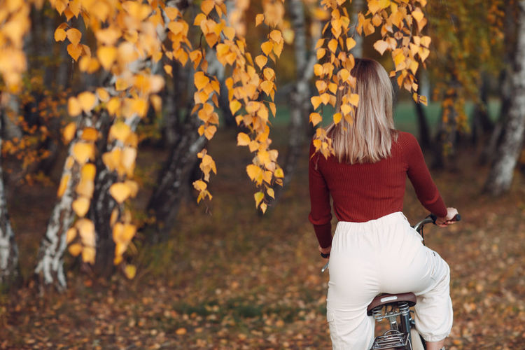 Rear view of woman standing amidst leaves during autumn