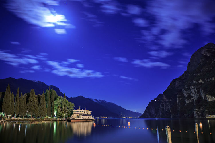 Riva del Garda town by night, Italy Dolomite, Garda Lake, Italy, Latern, Riva Del Garda, Town, Alpin, Alps, Architecture, Cafe, Downtown, European, Lake, Landscapes, Mountains, Night, Old, Outdoors, Range, Rock, Sky, Travel, Vacations Riva Del Garda Astronomy Beauty In Nature Blue Cloud - Sky Formation Idyllic Lake Mountain Mountain Range Nature Night No People Outdoors Reflection Scenics - Nature Sky Star - Space Tranquil Scene Tranquility Tree Water Waterfront