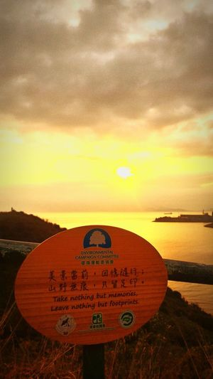 Close-up of road sign on beach against sky during sunset