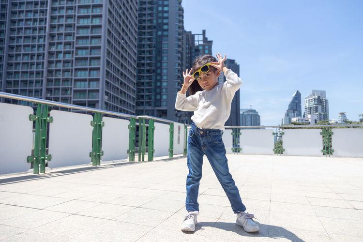 Asian kid wear sunglasses dancing street performance portrait
