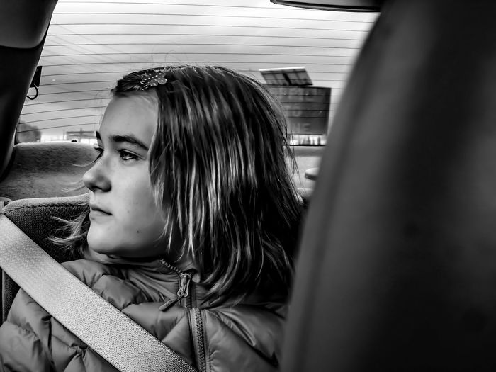 Close-up of thoughtful girl traveling in car