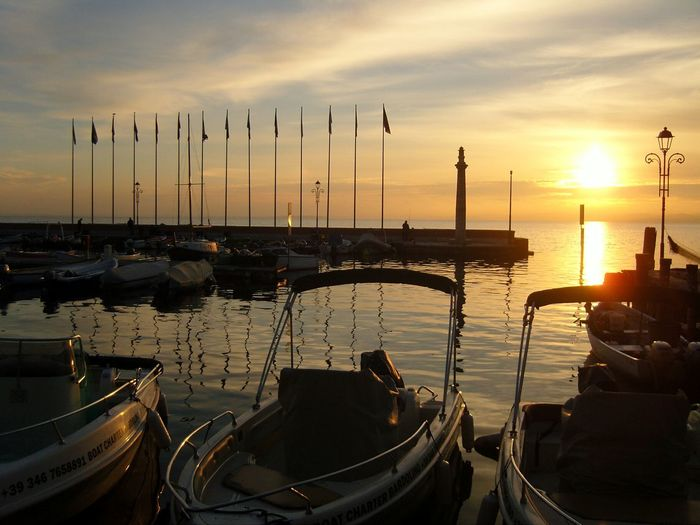 Boats Moored At Harbor On Sea Against Sky During Sunset