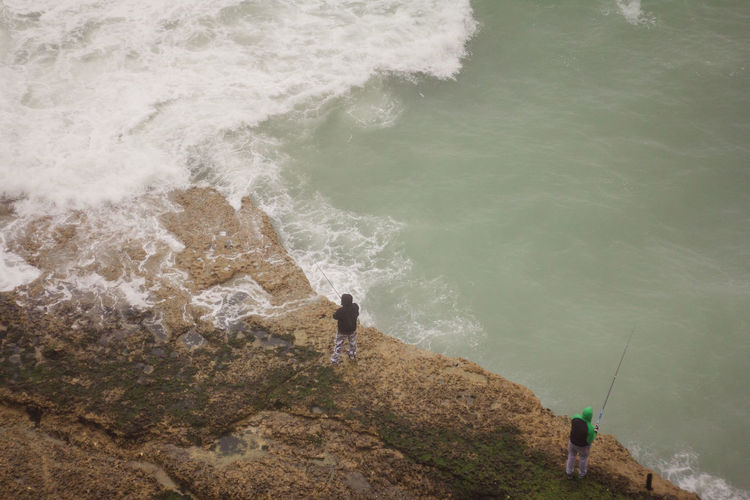 High Angle View Of Men Fishing In Sea