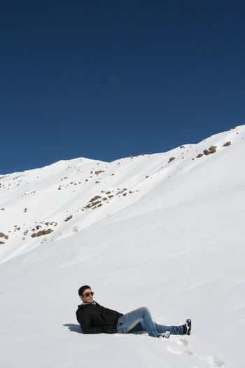 Full length of man lying down on snow covered landscape against clear blue sky