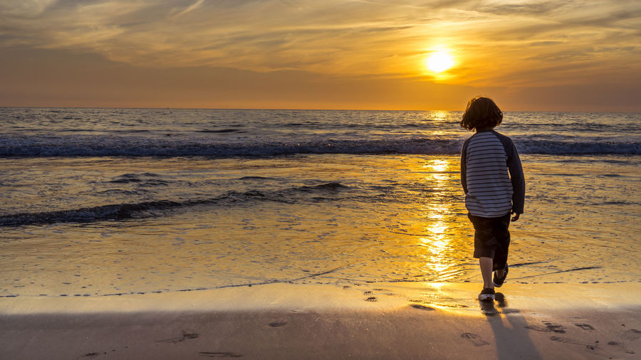 Rear View Of Boy Walking At Beach During Sunset