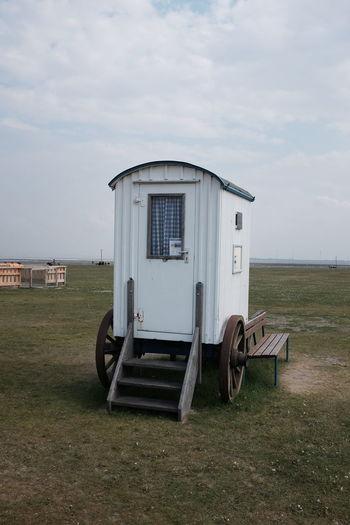 Portable toilet on grassy field against sky