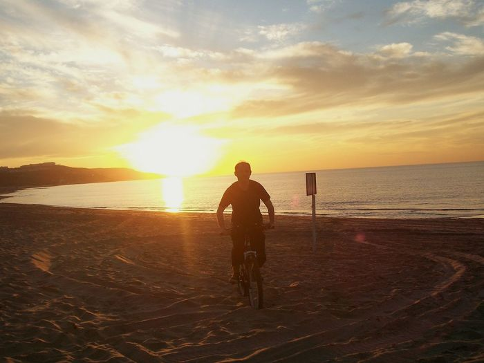 Man riding bicycle at beach against sky during sunset