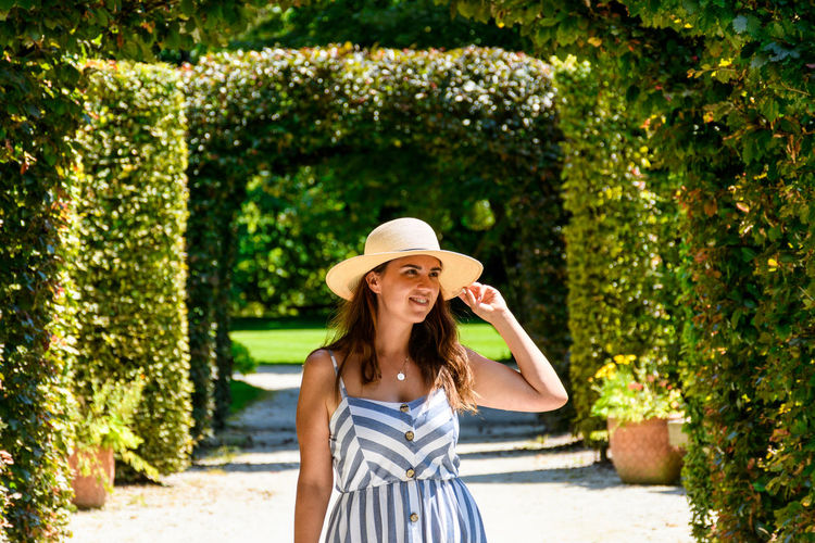 Smiling young woman wearing hat standing on footpath in park