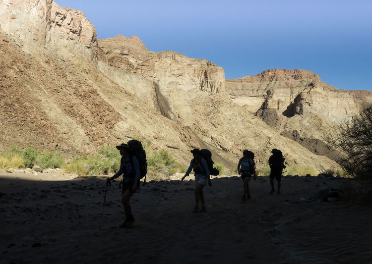 Group of hikers walking in shadow in scenic canyon Adventure Arid Climate Desert Friends Group Group Of People Hikers Hiking Landscape Landscape_Collection Let's Go. Together. Mountain Mountain Range Namibia Nature Outdoor Photography Outdoors Physical Geography Rock - Object Shadow Team Travel Walking Wilderness