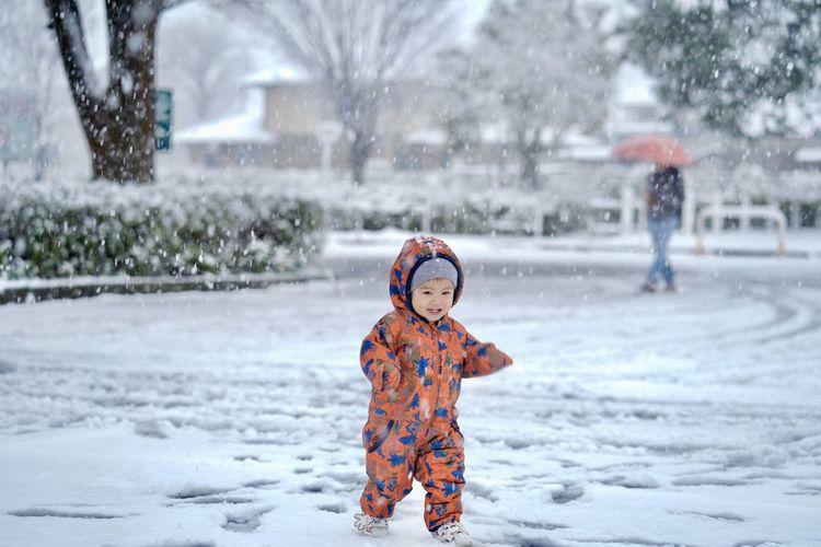 Full length of cute boy during winter. enjoy on snow floor in snowy day.