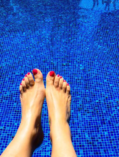 Low section of woman's legs in swimming pool