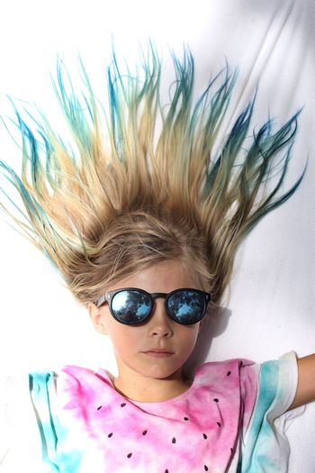 Directly Above Shot Of Girl With Dyed Hair Wearing Sunglasses Lying On Bed At Home