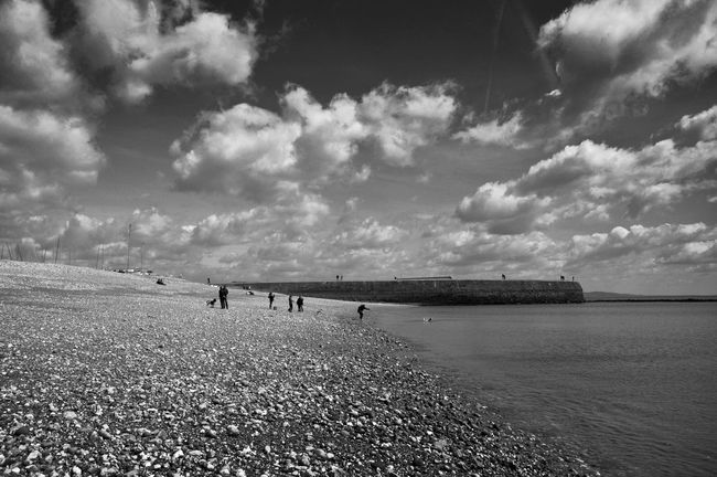 Beach Life Beauty In Nature Black And White Fine Art Photography Cloud - Sky Cloudy Day Idyllic Lifestyles Lyme Regis Nature Outdoors Rippled Scenics People And Places. seaside Sky Spring Day The Cobb Tranquil Scene Tranquility Travel Destinations Unrecognizable Person Vacations Water Monochrome Photography Black And White Friday