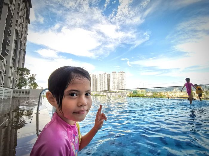 Portrait of girl in swimming pool against sky