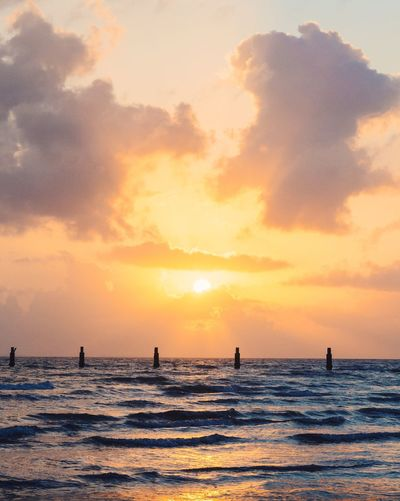 Silhouette wooden posts in sea against cloudy sky during sunset