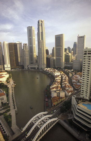 River Amidst Buildings Against Cloudy Sky
