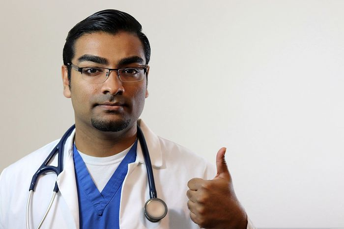 Handsome young doctor in blue scrubs and white lab coat giving thumbs up American Attractive Doctor  Hairstyle Handsome Health Healthcare Healthcare And Medicine Hospital Indian Lab Coat Medical Medicine Nurse Nurse Practitioner Physician Physician Assist Portrait Prescription  Scrubs Smart Specialist Stethe Surgeon Young Man