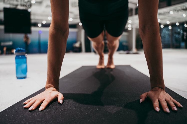 Low section of young woman exercising on mat with mobile phone at gym