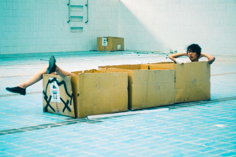 Man Sitting In Box In Swimming Pool