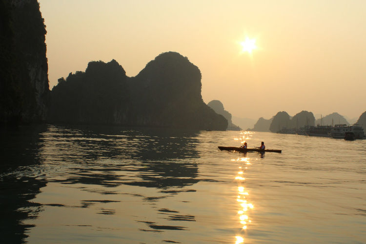 People Canoeing On Halong Bay By Rock Formations Against Clear Sky