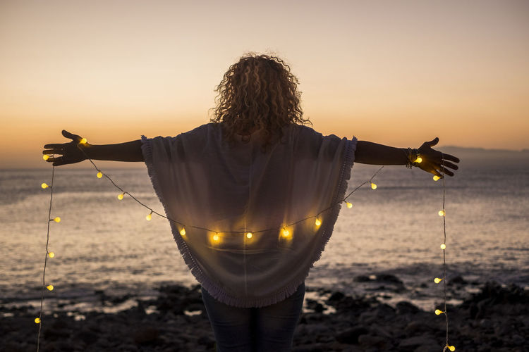 Rear view of woman holding illuminated lighting equipment while standing at beach against sky during sunset