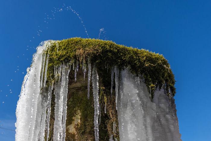 gefrorener Brunnen Drops Eis Himmel Winter Blue Brunnen Kalt Kaltes Klares Wasser Moos Nature No People Outdoors Sky Water