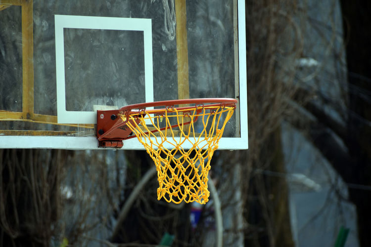 Low angle view of basketball hoop against window