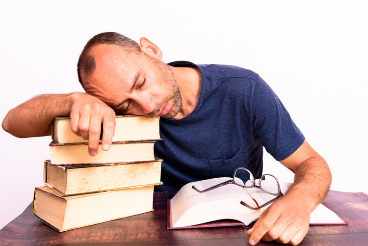 Midsection of man reading book on table against white background
