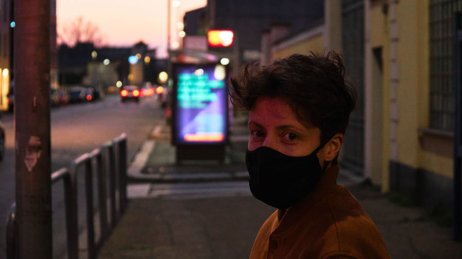 Portrait of woman with short hair standing on street at night wearing a mask