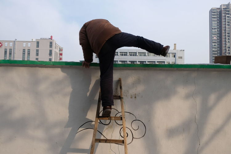 Just take a grandfather climbing posture, his feet painted with a cloud Climb The Wall City Day Ladder On The Wall Men One Person Outdoors People Real People
