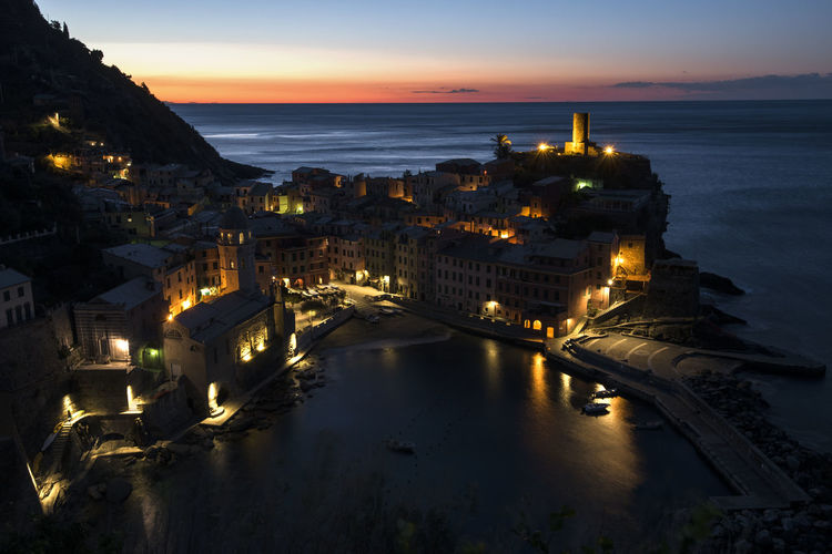 High angle view of illuminated townscape by sea against sky during sunset