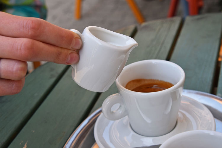 Cropped Hand Pouring Milk From Pitcher In Coffee At Table