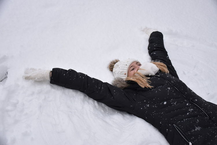 Black Color Cold Temperature Day High Angle View Leisure Activity Lifestyles Lying Down Lying On Back Nature One Person Outdoors People Real People Snow Warm Clothing Winter