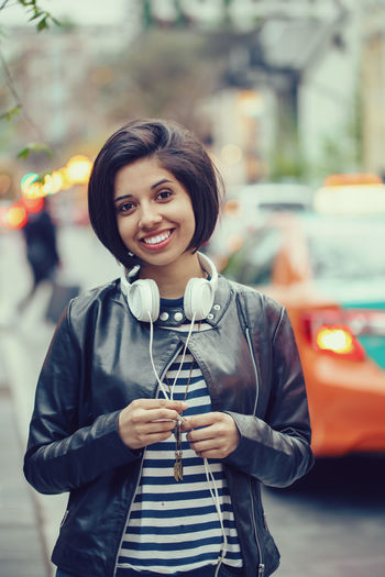Portrait of smiling young woman standing on street