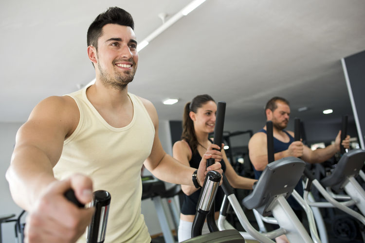 People exercising on machine in gym