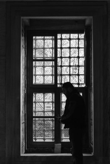 Side view of man standing by window