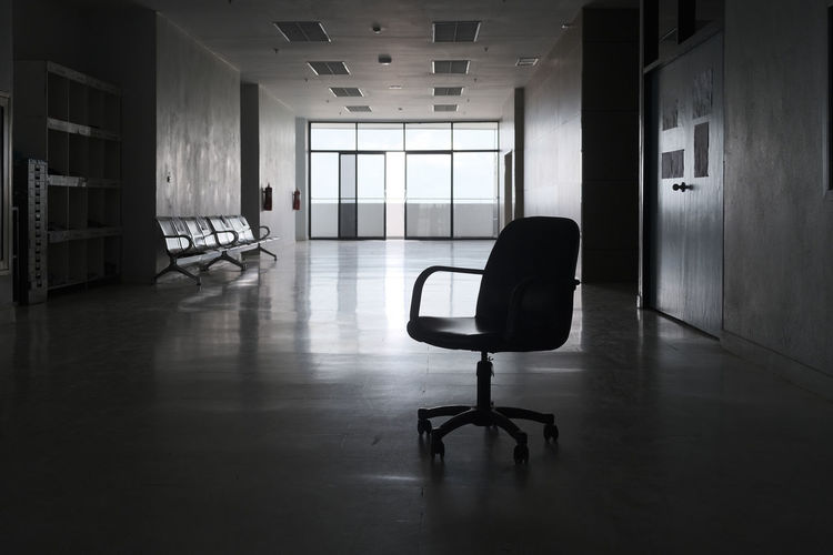 Empty chairs and table in building
