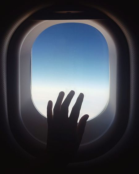 Cropped hand touching window of airplane